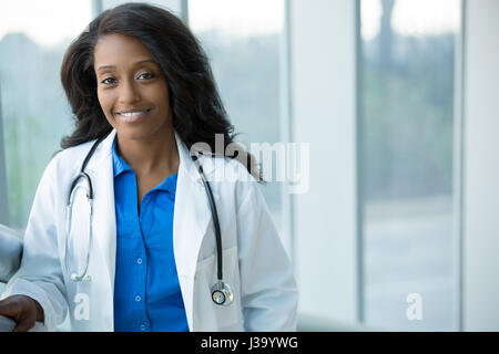 Closeup portrait of friendly, smiling confident female healthcare professional with lab coat, stethoscope, arms - Stock Photo