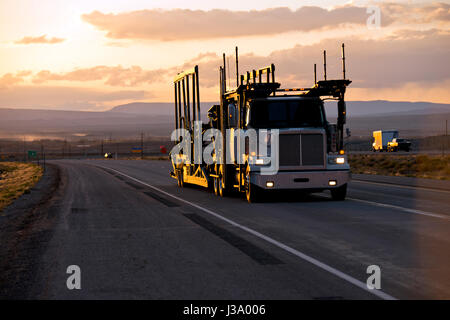 The big rig powerful semi truck with a car hauler trailer for the transporting of cars on the straight road in the - Stock Photo