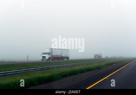Big rig semi truck with double trailers moves ahead of the column of cars on a split road with poor visibility shrouded - Stock Photo
