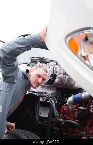 Inspector man checks diesel engine of commercial modern white big rig semi truck with the open hood for compliance - Stock Photo