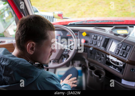 The truck driver sitting in the cab of modern comfort and ergonomic semi truck behind the wheel and interior dashboard - Stock Photo