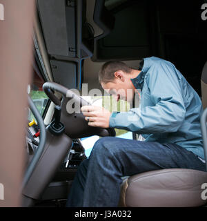 Young man truck driver sits in a comfortable cabin of modern truck and check the readiness of the truck electronics - Stock Photo