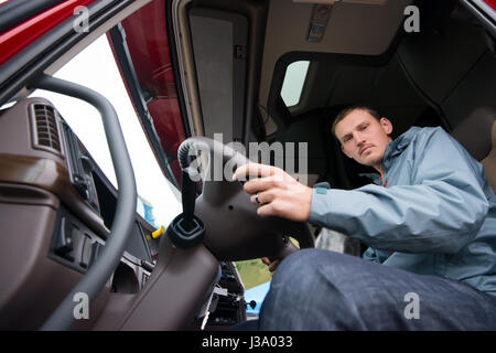 A young truck driver behind the wheel of modern comfortable cab of the big rig semi truck with a high cabin and - Stock Photo