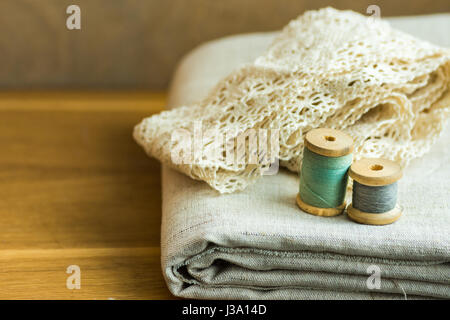 Folded linen fabric, lace ribbons, thread wooden spools on table, sewing, hobby, fashion concept, copyspace, close - Stock Photo