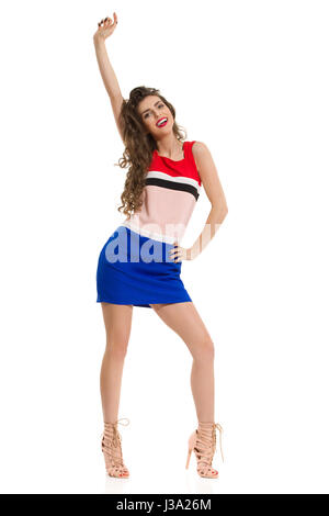Beautiful young woman in colorful mini dress and high heels is standing legs apart and raising arm. Front view. - Stock Photo