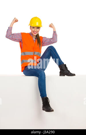 Smiling young woman in yellow hardhat, orange reflective vest, lumberjack shirt, jeans and black boots, sitting - Stock Photo