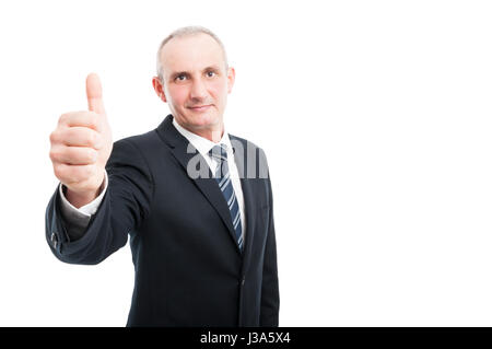 Portrait of mature elegant man showing thumb up wearing suit and tie isolated on white background with copy text - Stock Photo