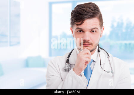 Portrait of handsome pensive doctor in white coat keeping hand on his chin and thinking with copy space - Stock Photo