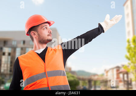 Low angle of construction worker showing or indicate something up outdoors - Stock Photo