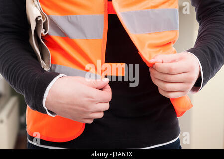 Closeup view of engineer with reflective vest getting ready for work - Stock Photo