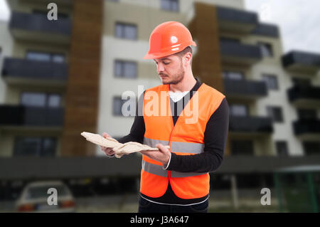 Male constructor outdoor at working place holding his protection gloves - Stock Photo