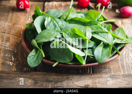 Fresh baby spinach leaves in rustic ceramic bowl - Stock Photo