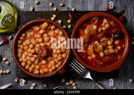 high-angle shot of two earthenware bowls with two typical spanish dishes, potaje de garbanzos, a chickpeas stew - Stock Photo