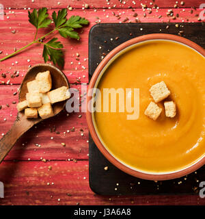 high-angle shot of an earthenware bowl with pumpkin puree topped with some croutons on a red rustic wooden table - Stock Photo