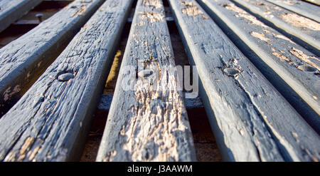 Low angle view perspective of weathered wood bench abstract in outdoor setting. - Stock Photo