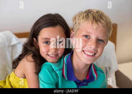 Portrait of smiling siblings embracing each other on bed in bedroom at home - Stock Photo