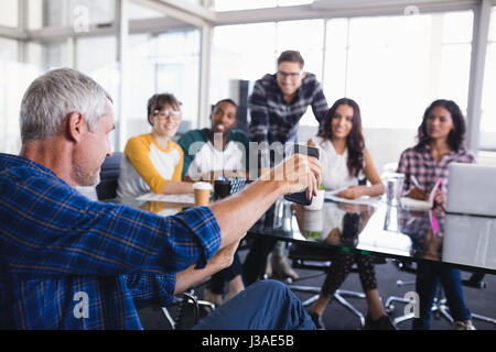 Businessman showing mobile phone to team working in background at creative office - Stock Photo