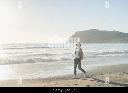 Young woman in red checkered shirt, jeans, white sneakers walking along beach and the stormy ocean on sunny winter - Stock Photo