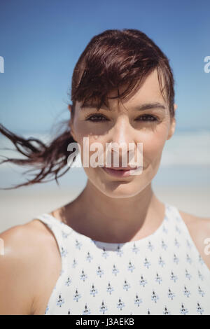 Portrait of young woman with tousled hair standing at beach during sunny day - Stock Photo