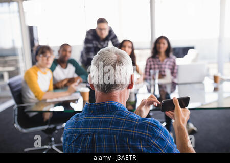 Businessman showing smartphone to team working in background at creative office - Stock Photo