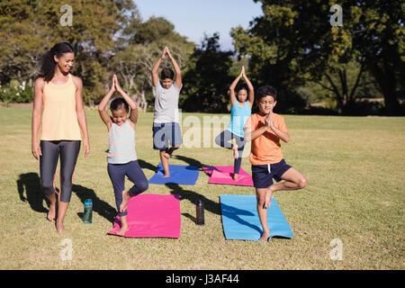 Trainer looking at children practicing Vriksasana at park - Stock Photo
