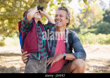 Happy mature father watching at boy looking through binoculars - Stock Photo