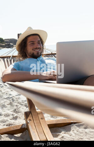 Smiling man using laptop while relaxing on hammock in beach - Stock Photo