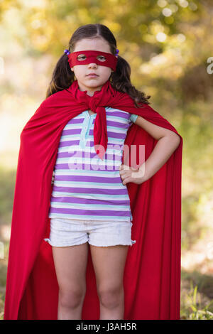 Portrait of confident little girl wearing superhero costume at campsite - Stock Photo