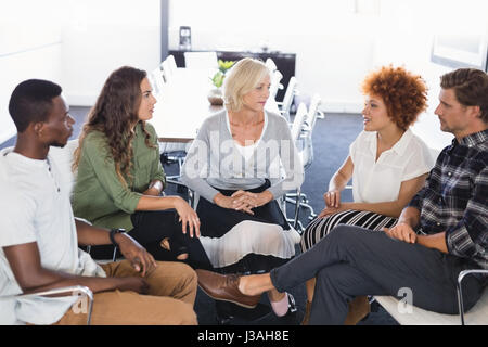 Serious business people discussing while sitting on chairs in office - Stock Photo
