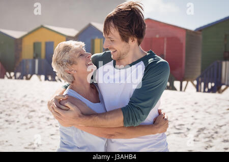 Happy mother embracing her son at beach during sunny day - Stock Photo