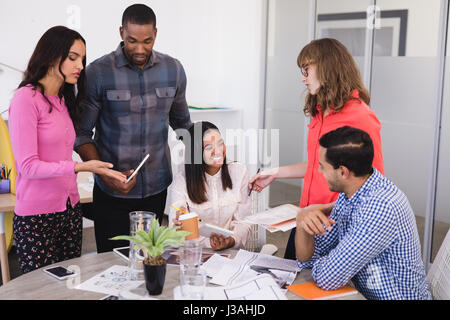 Smiling business people discussing at desk in office - Stock Photo
