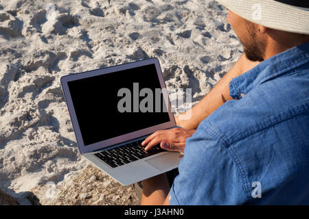 Man using laptop on the beach on a sunny day - Stock Photo