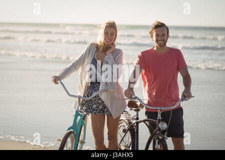 Portrait of smiling couple with bicycles standing at beach during sunny day - Stock Photo