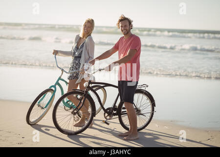 Portrait of young couple with bicycles standing at beach during sunny day - Stock Photo