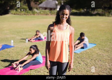 Portrait of female yoga trainer standing at park - Stock Photo