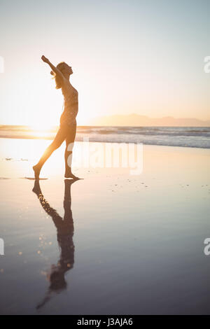Side view of carefree woman with arms outstretched walking at beach during dusk - Stock Photo