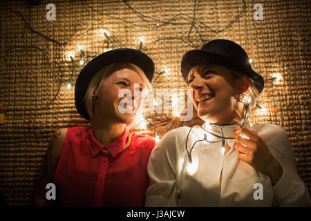 Two friends lying on the floor with fairy lights - Stock Photo