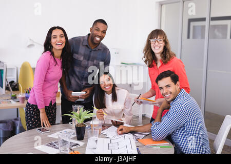 Smiling business people at desk against wall in office - Stock Photo