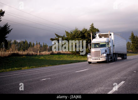Big Rig classic semi truck with reefer unit on refrigerator trailer for transporting food cargo moving wide streight - Stock Photo