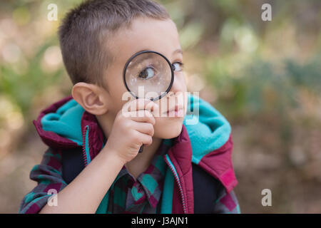 Portrait of little boy looking through magnifying glass - Stock Photo