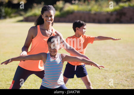Portrait of happy female trainer and girl practicing Virabhadrasana II pose at park - Stock Photo