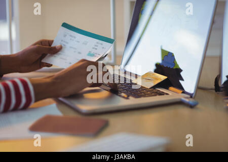 Cropped hands of businesswoman holding documents while using laptop in office - Stock Photo