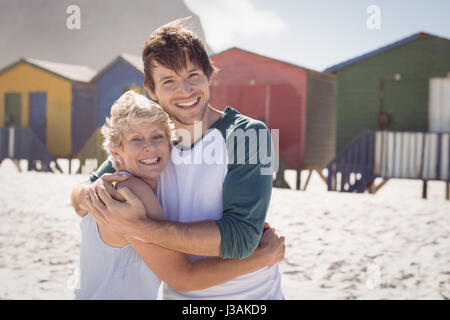 Portrait of happy mother embracing her son at beach during sunny day - Stock Photo