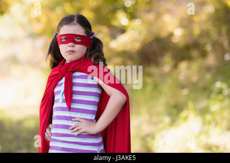 Portrait of little girl wearing superhero costume at campsite - Stock Photo