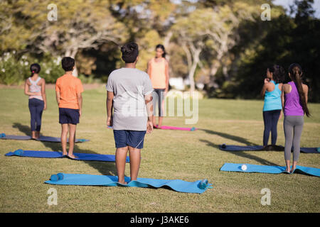Children standing on exercise mat practicing yoga at park during summer camp - Stock Photo