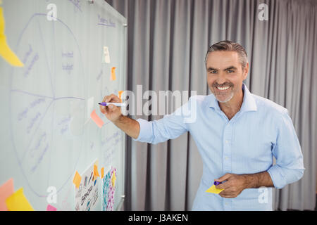 Portrait of smiling executive writing on sticky note in office - Stock Photo