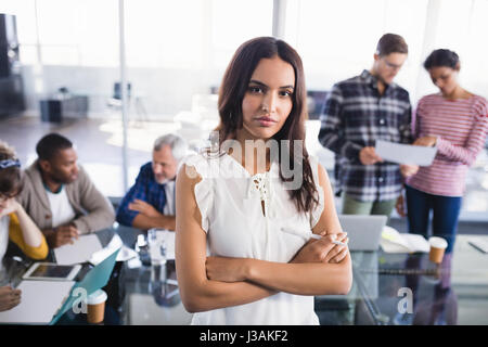 Portrait of young businesswoman standing with team working in background at creative office - Stock Photo