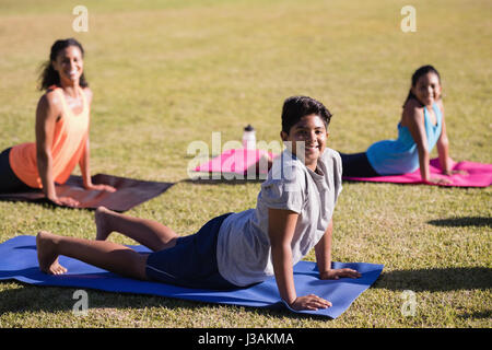 Portrait of children and instructor practicing yoga on mat at park - Stock Photo