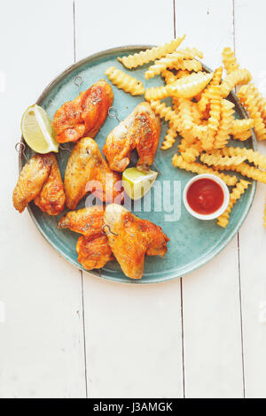 Grilled chicken wings with potato fries and dipping sauces Top view copy space - Stock Photo