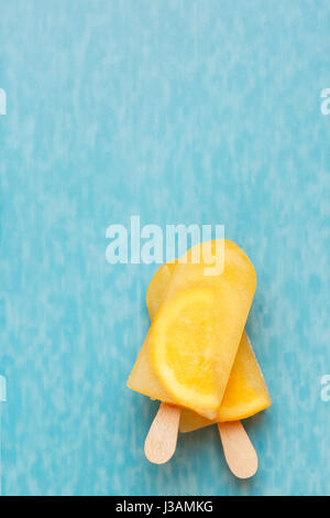 Fruit ice cream lollies on a blue surface. Top view, copy space - Stock Photo